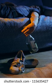 Young drunk man, lying on the couch with a bottle in hand