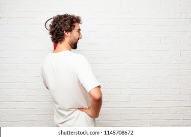 young dumb man back view, both hands on hips with the akimbo pose, probably feeling proud and satisfied.