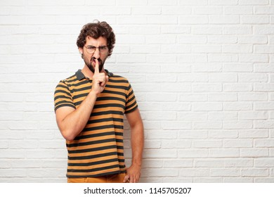 "young dumb man gesturing ""keep quiet"" with hand, hushing you and demanding silence with a serious, stern look."