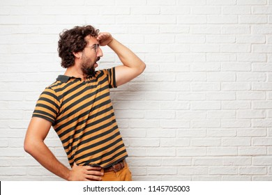 young dumb man looking far off into the distance, searching for a distant object with a confused look. Lateral or side view.
