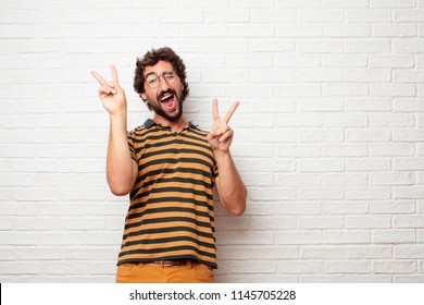 "young dumb man with a proud, happy and confident expression; smiling and showing off success while gesturing victory with both hands, giving an ""achiever"" look, celebrating triumphantly."