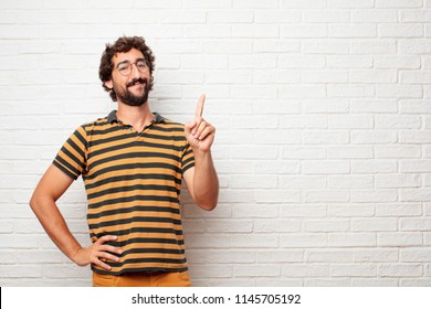 young dumb man smiling and looking satisfied and happy, counting number with one finger.