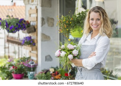 Young dynamic florist in front of her shop