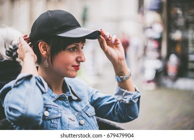 young early thirties woman in boyish clothes adjusting her hat with a city background