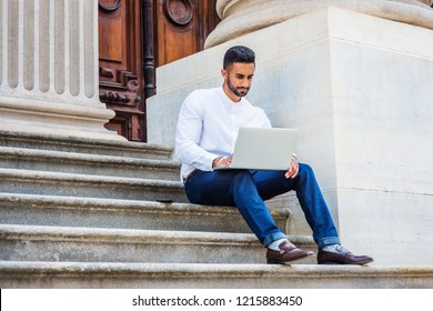 Young East Indian American College Student with beard studying in New York, wearing white shirt, blue pants, leather shoes, sitting on stairs outside office building, working on laptop computer.