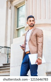 Young East Indian American Man with beard working in New York, wearing brown blazer, white round collar shirt, holding laptop computer, cell phone, standing outside office building, looking away.