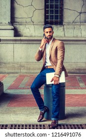 Young East Indian American Man with beard traveling, working in New York, wearing brown blazer, blue jeans, leather shoes, holding laptop computer, sitting on pillar on street, talking on cell phone.