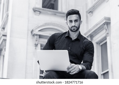 Young East Indian American Man with beard, studying, working in New York City, wearing black shirt, holding laptop computer, sitting outside old style office building, looking up. Black and White.