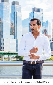 Young East Indian American Man wearing white shirt, black jeans, standing in business district with high buildings by Hudson River in New York, hand touching cuff, looking away.