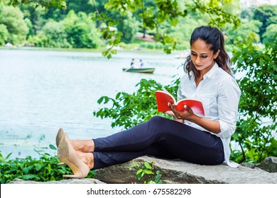 Young East Indian American Woman reading red book, relaxing at Central Park, New York, wearing white shirt, black pants, high heels, sitting on rocks by lake. People rowing boat on background.