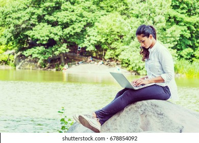 Young East Indian American Woman wearing white shirt, black pants, white sneakers, crossing legs, sitting on rocks by lake at Central Park, New York, looking down, typing, working on laptop computer.