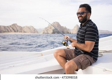 Young East Indian man fishing on open water from the boat. Beautiful sunny day with the shoreline visible in the background. South Asian male.