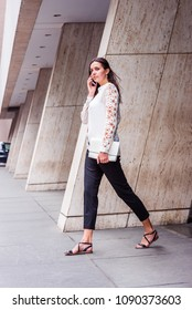 Young Eastern European Businesswoman working in New York, wearing white, lace cut out long sleeve shirt, black pants, sandals, holding leather purse, talking on phone, walking out from office building