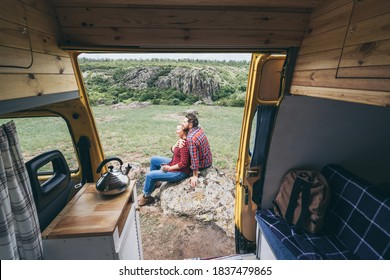 Young Eastern European couple travelling by camper van though the countryside. Self built off-grid motorhome camping in the wild nature.