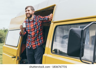 Young Eastern European man travelling by yellow camper van though the countryside. Self built off-grid motorhome camping in the wild nature.