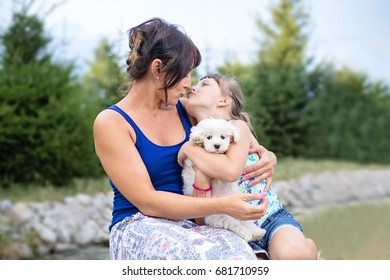 Young eastern european mother and her cute little daugher sitting outdoors in nature on summer day, cuddling and kissing