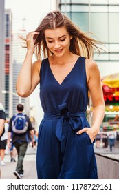 Young Eastern European Woman with long brawn hair traveling in New York City, wearing blue sleeveless, v neck, jumpsuit, walking on street in middletown of Manhattan, looking down, thinking, smiling.
