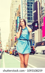 Young Eastern European Woman traveling in New York, wearing short blue Denim dress, walking on busy street in Times Square of Manhattan, talking on cell phone. High Buildings, cars on background.