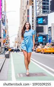 Young Eastern European Woman traveling in New York, wearing short Denim dress, carrying purse, holding cell phone, walking on street in Times Square of Manhattan. High Buildings, cars on background.