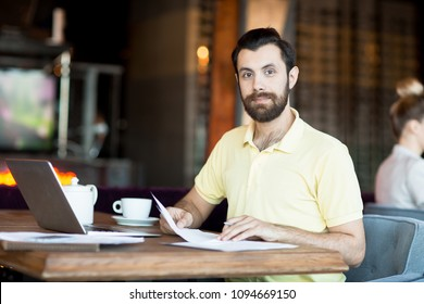 Young economist with documents looking at you while looking through new contracts in cafe