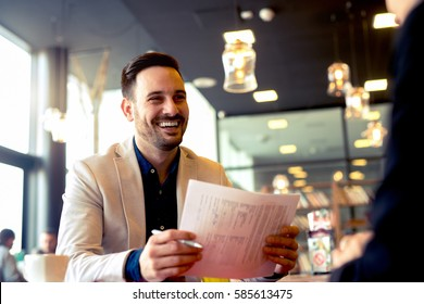 Young economist looks very happy after doing paper work and making calculations working with colleagues