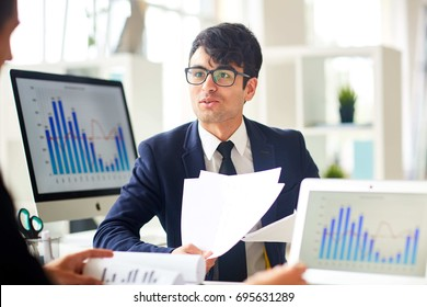 Young economist talking to colleague and explaining financial papers