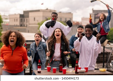 Young ecstatic friends shouting excitedly while cheering during match broadcast