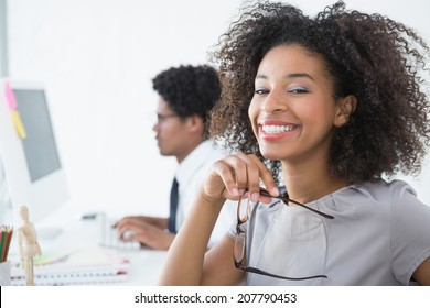 Young editor smiling at camera at her desk in creative office