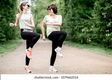 Young and elder sports woman stretching in the park during the morning exesrcise