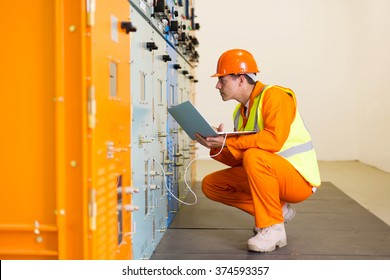 young electrical engineer working on laptop in substation control room
