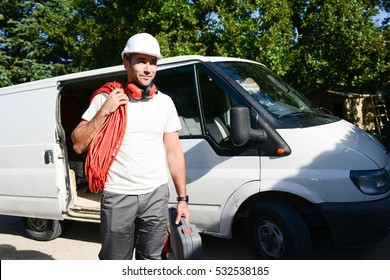 young electrician artisan taking tools out of his professional truck van