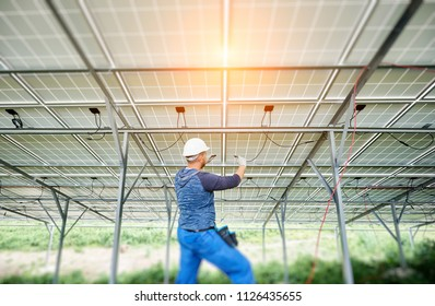 Young electrician connecting electrical cables inside the lit by sun solar modules. Installing and wiring of solar photo voltaic panel system. Alternative energy and profitable investment concept.