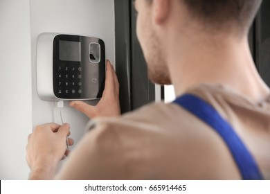 Young electrician installing security alarm on wall