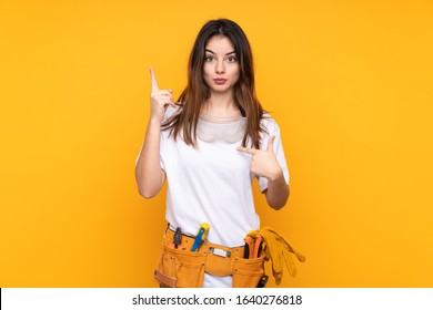 Young electrician woman over isolated on yellow background with surprise facial expression
