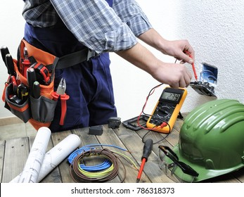Young electrician at work measures the voltage of a residential electrical installation.