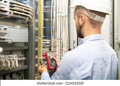 young electrician working on electric panel. Electrician engineer tests electrical installations and wires on relay protection system. Technician with multimeter in fuse box. Man tests electric panel