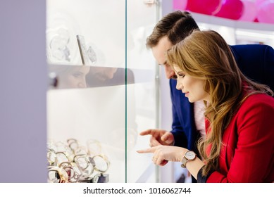 Young elegance couple watching watches on store window in the jewelry store.