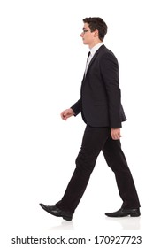 Young elegance man walking. Full length studio shot isolated on white.