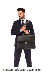 young elegant assasin holding gun and suitcase looks to side on white background