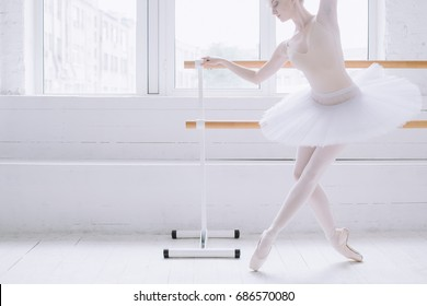 Young and elegant ballerina standind in croise derriere position on pointe at barre near big window in white classroom. She is concentrated on making this position. Close up