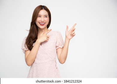 Young elegant beautiful Asian woman smiling and pointing to empty copy space isolated on white background
