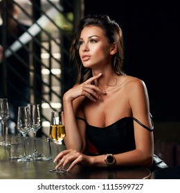 Young elegant beautiful woman sitting in bar and waiting for boyfriend. Sexy girl in black leather dress spending time with glass of wine and dreaming