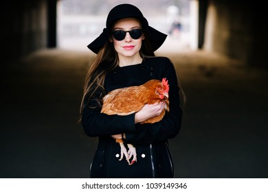 Young elegant brunette fashionable model girl in sunglasses holding chiken in hands. Stylish female with lovely pet. Woman in black with bird hen outdoor in tunnel. Animal lover. New stream lifestyle