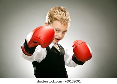 young elegant business boy punch with boxe gloves portrait on grey background