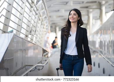 Young elegant business woman with hand luggage walking along sidewalk outdoors in urban city,business trip,travel.