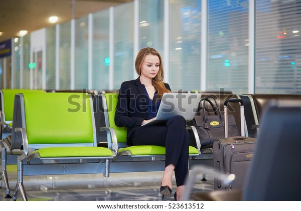 Young elegant business woman with hand luggage in international airport terminal, working on her laptop while waiting for flight