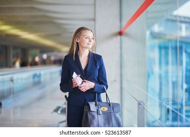 Young elegant business woman near the window in international airport terminal, holding passport and boarding pass. Cabin crew member with suitcase.