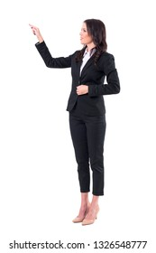 Young elegant business woman or teacher pointing finger and showing blank space. Full body isolated on white background.
