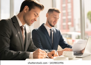 Young elegant businessman concentrating on making notes in notebook while organizing work on background of colleague