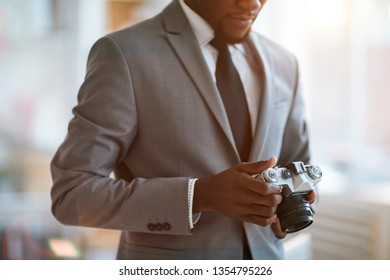 Young elegant businessman in formalwear looking at photocamera in his hands while going to take photos of something
